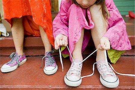 Two girls, one tying up shoelace Stock Photo - Premium Royalty-Free, Code: 614-03747790