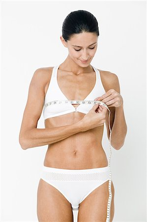 Young woman measuring breasts with tape measure Stock Photo - Premium Royalty-Free, Code: 614-03763589