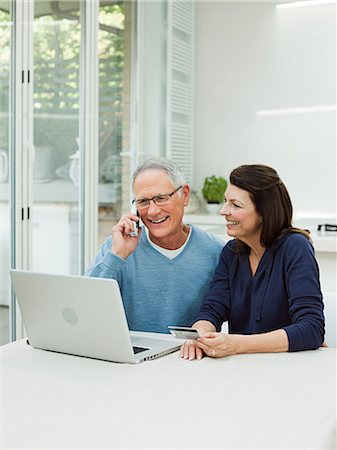 person on phone with credit card - Mature couple using laptop with credit card Stock Photo - Premium Royalty-Free, Code: 614-03763783