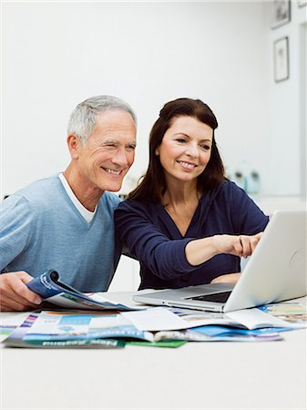 Mature couple using laptop to book vacation Stock Photo - Premium Royalty-Free, Code: 614-03763790