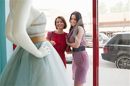 Mother and daughter looking at wedding dress in shop window Stock Photo - Premium Royalty-Free, Code: 614-03763841
