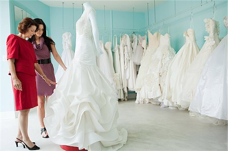 Mother and daughter looking at wedding dresses Stock Photo - Premium Royalty-Free, Code: 614-03763871