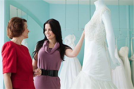 Mother and daughter looking at wedding dresses Stock Photo - Premium Royalty-Free, Code: 614-03763894
