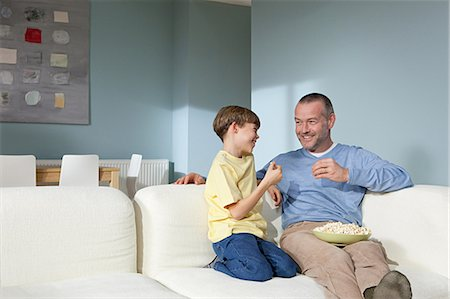 snack - Father and son watching television eating popcorn Stock Photo - Premium Royalty-Free, Code: 614-03784094