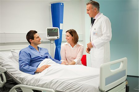 Wife visiting husband in hospital, talking to doctor Stock Photo - Premium Royalty-Free, Code: 614-03783641