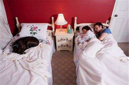 Young couple sharing single bed, dog asleep on other bed Stock Photo - Premium Royalty-Free, Code: 614-03981507