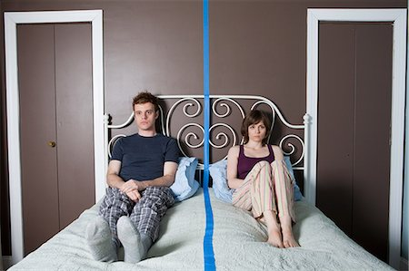 Young couple sitting on bed separated by blue line Foto de stock - Sin royalties Premium, Código: 614-03981512