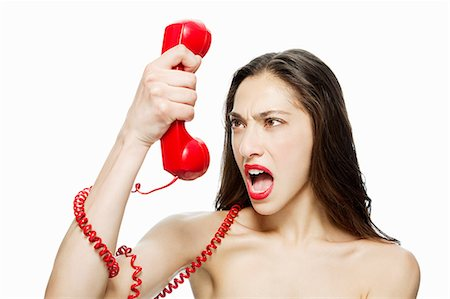 phone cord - Angry woman shouting into red telephone Stock Photo - Premium Royalty-Free, Code: 614-03982054