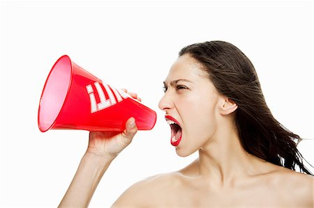 Woman shouting into red megaphone Stock Photo - Premium Royalty-Free, Code: 614-03982055
