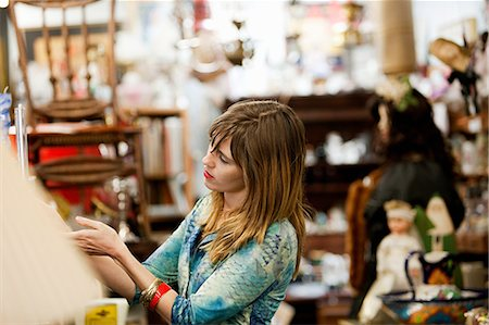 Woman inspecting items for sale in antiques shop Stock Photo - Premium Royalty-Free, Code: 614-03982144