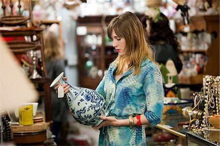 Woman inspecting vase in antiques shop Stock Photo - Premium Royalty-Free, Code: 614-03982145