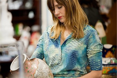 Woman inspecting vase in antiques shop Stock Photo - Premium Royalty-Free, Code: 614-03982146