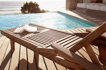 Open book on poolside lounge chair Stock Photo - Premium Royalty-Free, Code: 618-05761676
