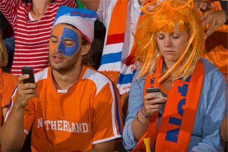 soccer fan - Dutch fans looking at phone at soccer game in Cape Town, South Africa Stock Photo - Premium Royalty-Free, Code: 618-05800198
