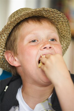 Young boy in straw hat eating french fries Stock Photo - Premium Royalty-Free, Code: 618-05800227