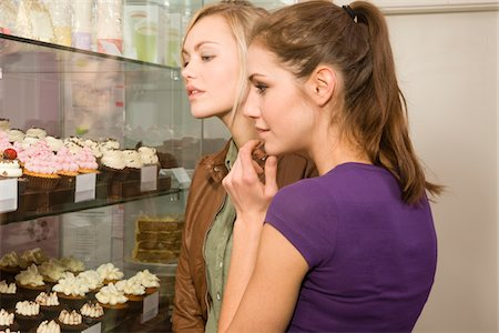 Young women looking at display of cupcakes Stock Photo - Premium Royalty-Free, Code: 618-05800296