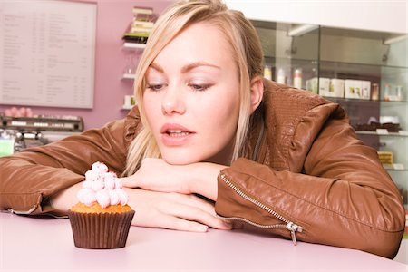 Young woman looking at cupcake Stock Photo - Premium Royalty-Free, Code: 618-05800323