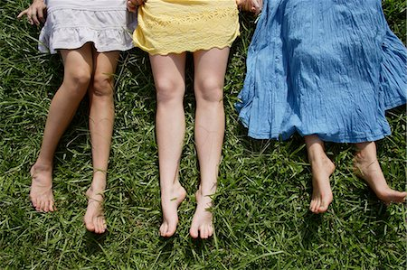 Cropped shot of legs of three teen girls lying on the grass Stock Photo - Premium Royalty-Free, Code: 618-06318470