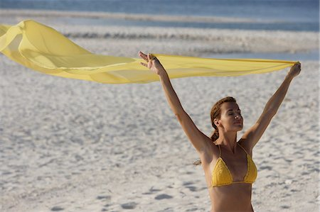 woman in yellow bikini holding yellow fabric on beach Stock Photo - Premium Royalty-Free, Code: 618-06318559