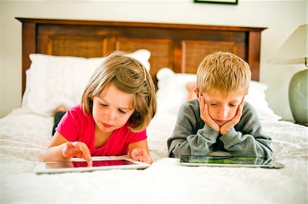 Two young kids using tablet device's together. Stock Photo - Premium Royalty-Free, Code: 618-06347132