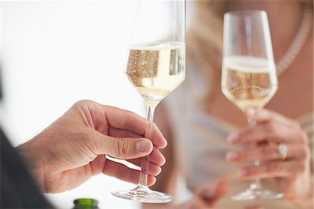 Couple toasting glasses of champagne, close up Stock Photo - Premium Royalty-Free, Code: 618-06405489