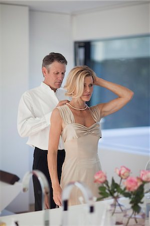 Mature man adjusting necklace of woman in mirror Stock Photo - Premium Royalty-Free, Code: 618-06405482