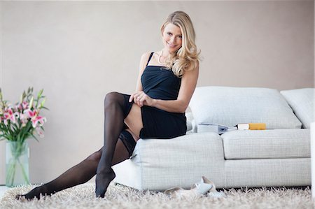 Mature woman sitting on sofa in black dress and stockings, portrait Stock Photo - Premium Royalty-Free, Code: 618-06405495