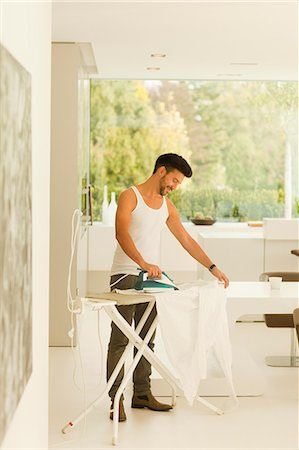 Mid adult man ironing clothes at home Stock Photo - Premium Royalty-Free, Code: 618-06405534