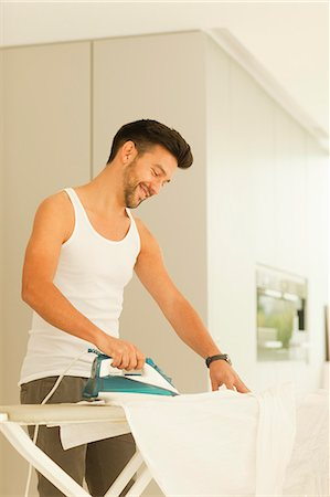 Mid adult man ironing clothes, smiling Stock Photo - Premium Royalty-Free, Code: 618-06405536