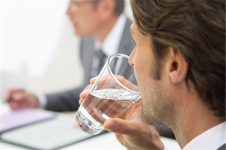 drinking water glass - Businessman sipping water in meeting, close up Stock Photo - Premium Royalty-Free, Code: 618-06405563