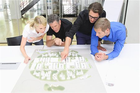 Four architects looking at architectural model in studio Stock Photo - Premium Royalty-Free, Code: 618-06405579