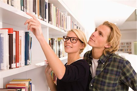 reaching - Student couple choosing text books from library bookshelf Stock Photo - Premium Royalty-Free, Code: 618-06405649