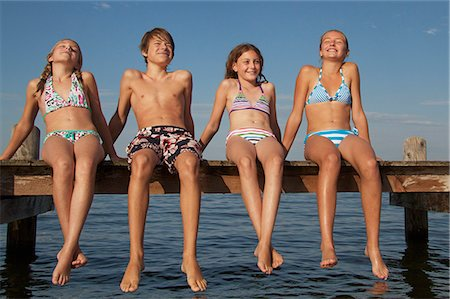 Young friends sitting in a row on pier Stock Photo - Premium Royalty-Free, Code: 618-06405669