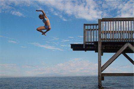 Young girl jumping into sea into pier Stock Photo - Premium Royalty-Free, Code: 618-06405676