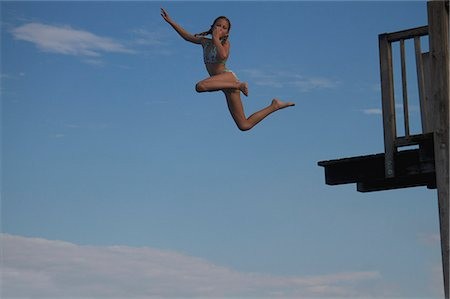 Young girl jumping into sea into pier Stock Photo - Premium Royalty-Free, Code: 618-06405678