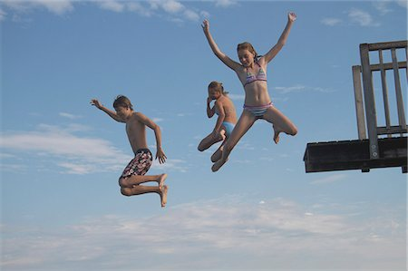 preteen bathing suit - Young friends jumping into sea from pier Stock Photo - Premium Royalty-Free, Code: 618-06405679