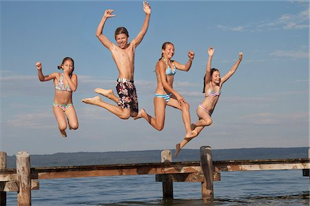 preteen bathing suit - Young friends jumping from pier into sea Stock Photo - Premium Royalty-Free, Code: 618-06405670