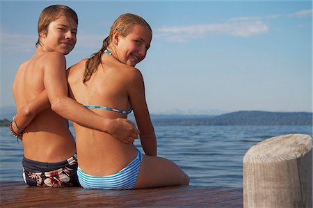 preteen swimsuit - Young teenage couple sitting on pier, smiling, portrait Stock Photo - Premium Royalty-Free, Code: 618-06405671