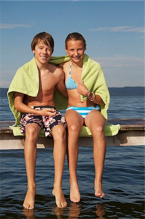 preteen bathing suit - Young teenage couple sitting on pier, smiling, portrait Stock Photo - Premium Royalty-Free, Code: 618-06405672