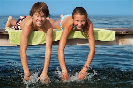 Young teenage couple lying on pier, smiling, portrait Stock Photo - Premium Royalty-Free, Code: 618-06405673