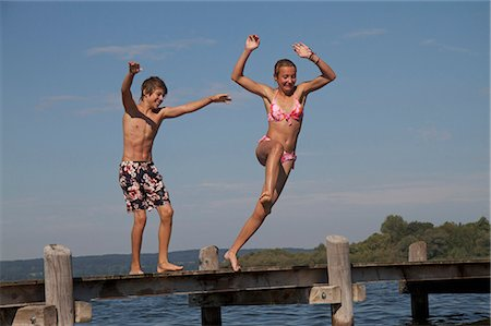 Young friends jumping into water from pier Stock Photo - Premium Royalty-Free, Code: 618-06405685