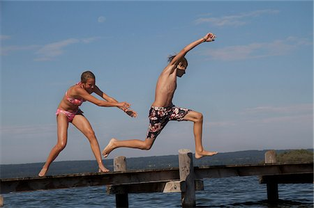 Young friends jumping into water from pier Stock Photo - Premium Royalty-Free, Code: 618-06405686