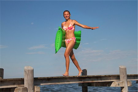 Teenage girl walking along pier holding airbed Stock Photo - Premium Royalty-Free, Code: 618-06405681