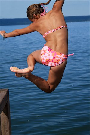 preteen swimsuit - Girl jumping into sea, rear view Stock Photo - Premium Royalty-Free, Code: 618-06405694