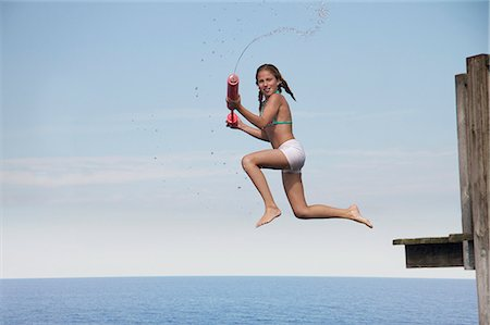 Girl jumping into sea holding water pistol, side view Stock Photo - Premium Royalty-Free, Code: 618-06405699