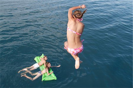 Girl jumping into sea, high angle view Stock Photo - Premium Royalty-Free, Code: 618-06405691