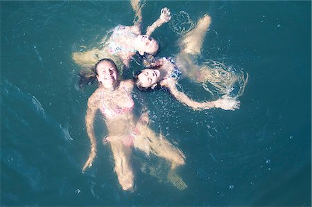 Young friends floating together in sea, high angle view Stock Photo - Premium Royalty-Free, Code: 618-06405692