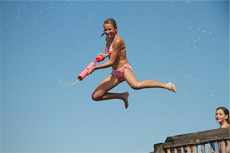 Girl jumping into sea holding water pistol, side view Stock Photo - Premium Royalty-Free, Code: 618-06405700