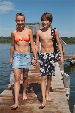 Young teenage couple walking along pier holding hands Stock Photo - Premium Royalty-Free, Code: 618-06405701