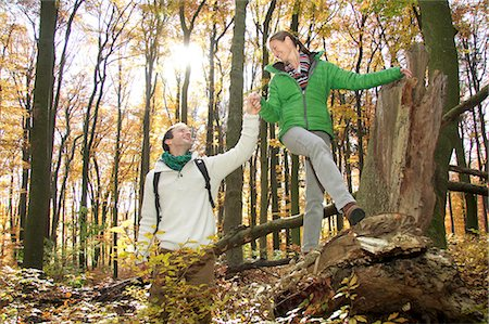 Mid adult man holding hand of woman climbing over log in forest Stock Photo - Premium Royalty-Free, Code: 618-06405815